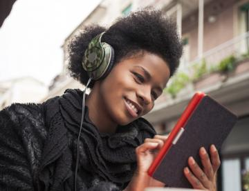 Person wearing headphones and reading from tablet outside.