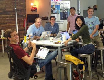 Google volunteers sitting around a table smiling