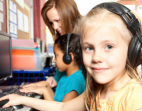 A smiling young girl wearing headphones works at a computer with another child and an adult looking on.