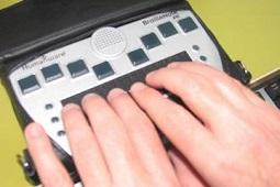 Hands touching refreshable braille display.