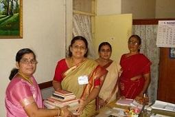 Women wearing Indian saris and holding books.