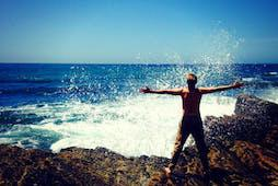Person stands with their arms wide. Ocean waves crash on rocks.
