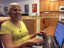 Image of Sandi Ryan sitting at her laptop at home.