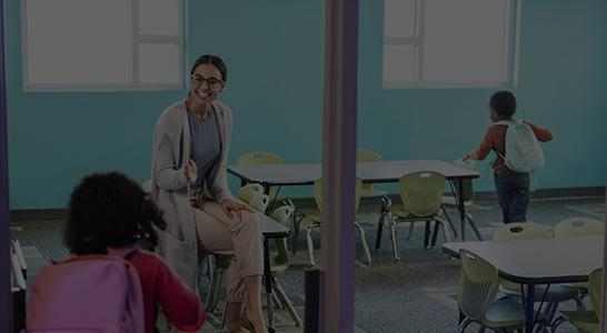 Teacher welcoming students into classroom.