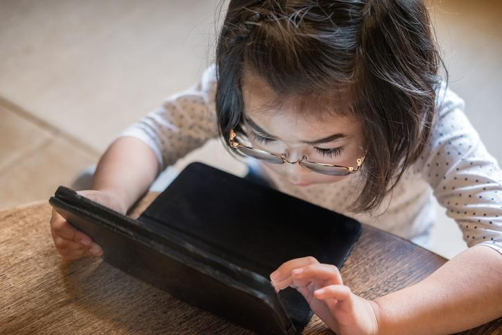 young girl reading on a laptop computer