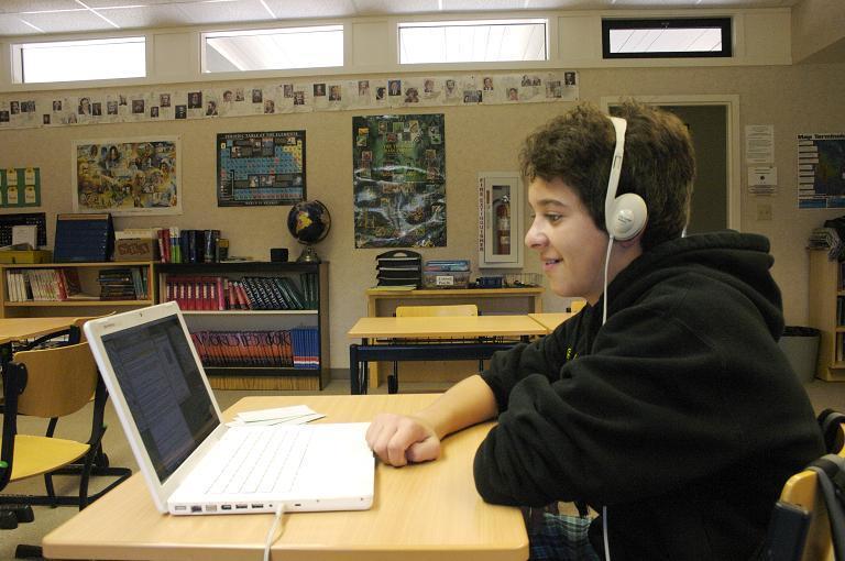 Student with headphones listening to a book on his computer