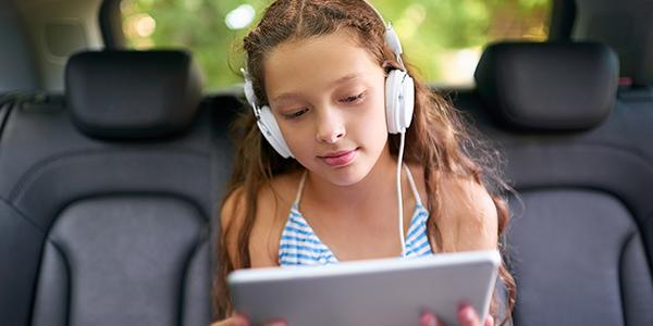 Girl in car reading ebook on tablet with headphones