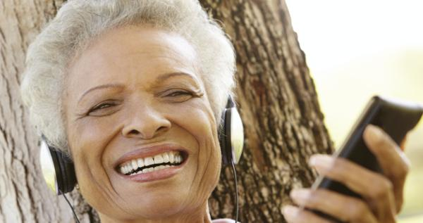 Older woman listening to an audiobook using a phone and headphones