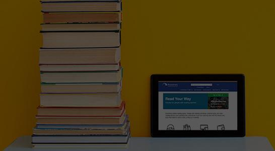 Stack of books. Tablet with Bookshare website open.