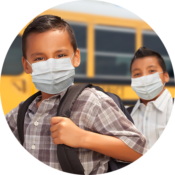 Two students wearing face masks next to school bus.