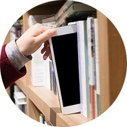 Hand taking tablet off of library shelf.